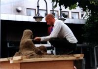 Stavanger: Ein Straßenkünstler moduliert eine Figur aus Sand